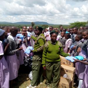 Women rangers distributing sanitary towels to school kids